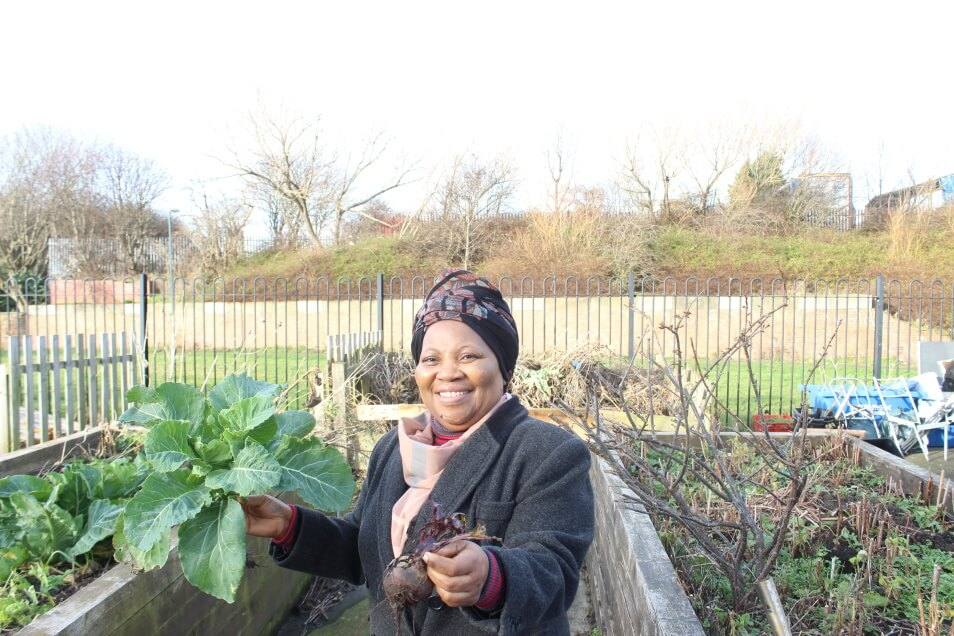 A smiling Black woman holding a leafy beetroot