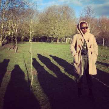 Noni standing in a field, with the sun in their face looking very cool with a pair of sunshades on
